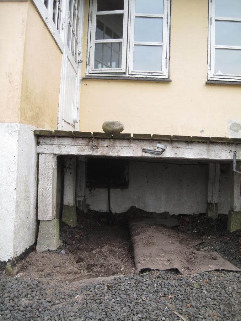 ... under terrassen og frem til kældervæggen.